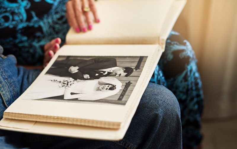 two people looking at old wedding album
